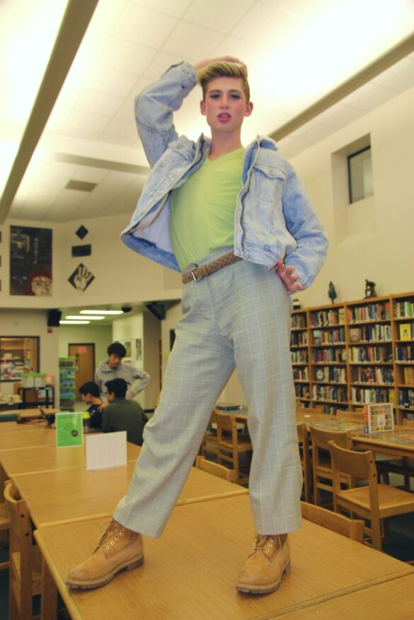 Sophomore Zachary Willmore poses atop a table in the library. Modeling while the whole media center watched, Willmore flexed his 60's themed fit.