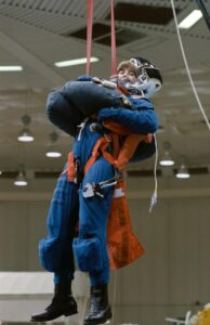 During a training session, Linda Godwin simulates an emergency exit from a space shuttle. Source: NASA.gov
