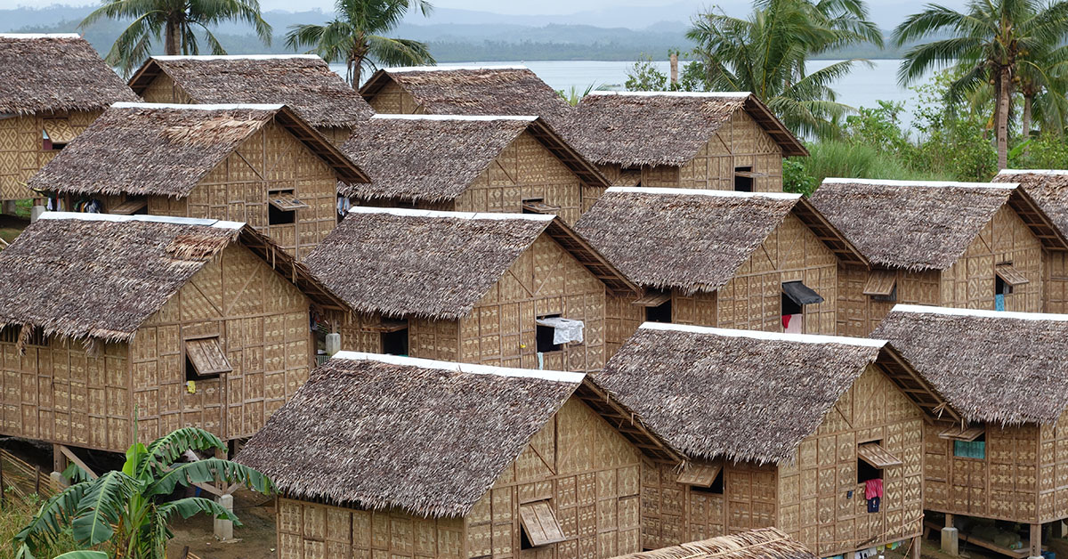 Rows of thatch houses in front of ocean