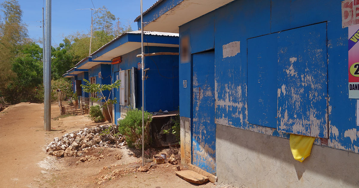 Rows of blue resettlement housing with worn paint