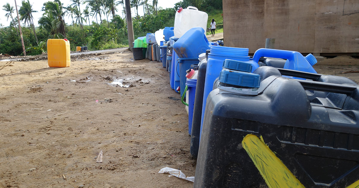 Line of water cans on ground
