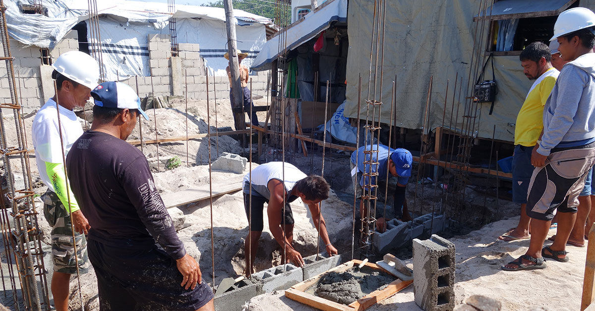 Construction laborers place block walls for a new house
