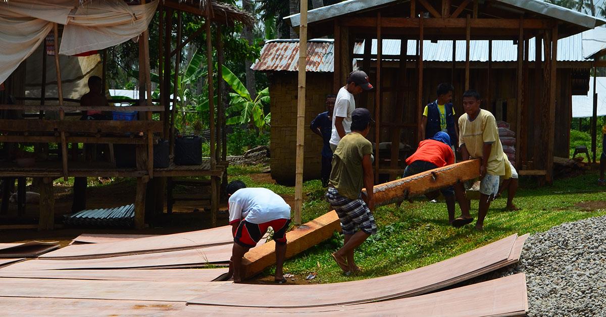 Men carrying large logs