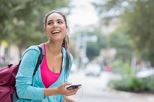 Happy young Hispanic woman smiles while waiting for a ride in a downtown district. She is holding a smart phone and wearing headphones. She is wearing a backpack and turquoise hoodie.