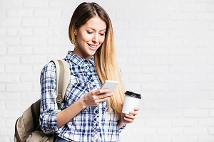 Happy young student girl with smartphone