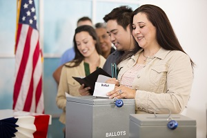 Multi-ethnic group of people stand in line to cast their ballot in the November USA elections at a local polling station. Hispanic woman foreground. Other voters in line background. Ballot box.