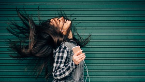 Young woman tossing hair while enjoying the music