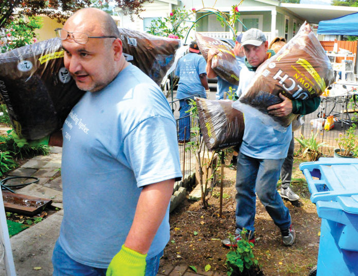Volunteers bring in mulch for some landscaping work at a home in Pacific Mobile Estates in Gilroy on April 27.