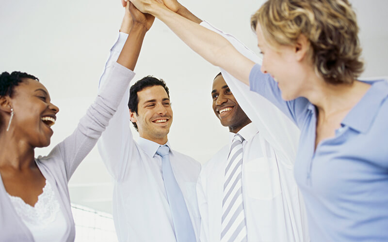 Image of a diverse business people, holding there hands up in the air.