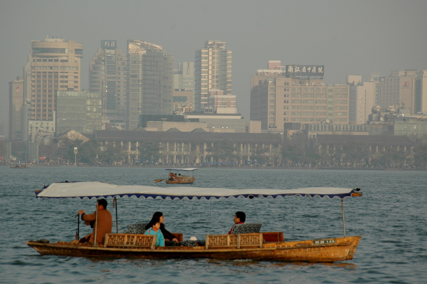Traditional wooden boats on West Lake against the backdrop of Hangzhou's modern skyline © 2016 Karen Rubin/goingplacesfarandnear.com