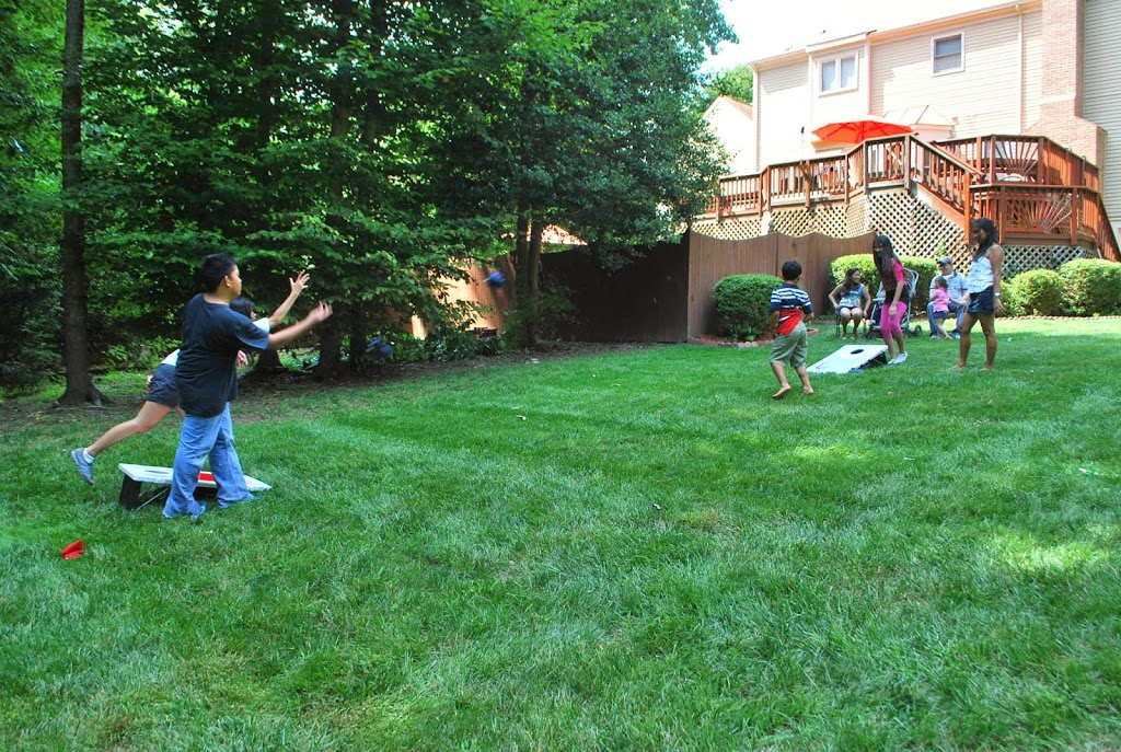 kids playing bean bag toss game during a Game Truck Party for a boy birthday