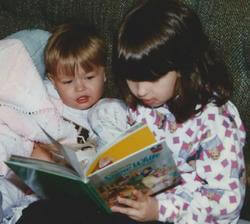 Two small children reading together