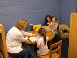 Children reading books with JeNel and their mother