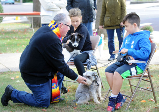 From left, Rev. Jeffrey A. Wargo blesses Brooke Alexander's dog Shadow and Nolan Wimmer's dog Jaxon during a blessing of the pets ceremony Sunday, October 23, 2016 at St. Stephen's United Church of Christ in Perkasie, Pennsylvania. (Photo by William Thomas Cain)