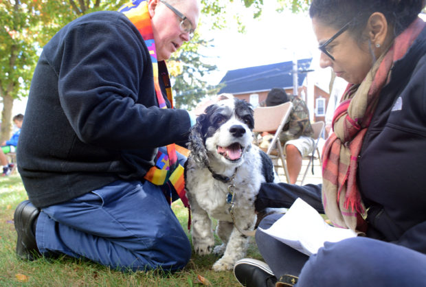 From left, Rev. Jeffrey A. Wargo blesses Cooper the dog as his owner, Calkins Media's Garden Minute host Tina Sottolano-Cain looks on during a blessing of pets ceremony Sunday, October 23, 2016 at St. Stephen's United Church of Christ in Perkasie, Pennsylvania. (Photo by William Thomas Cain)