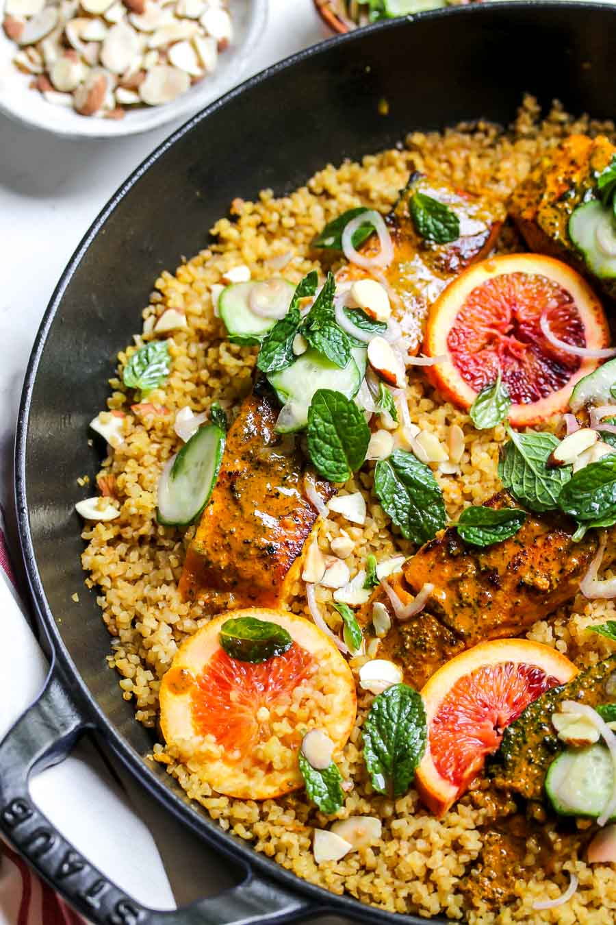 Turmeric-glazed salmon in a pan with bulgur wheat