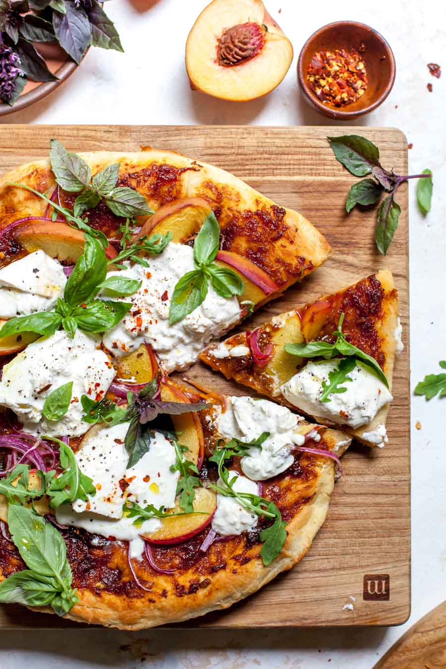 Stove top pizza with peach-BBQ sauce, fresh sliced peaches, red onion, burrata, and basil