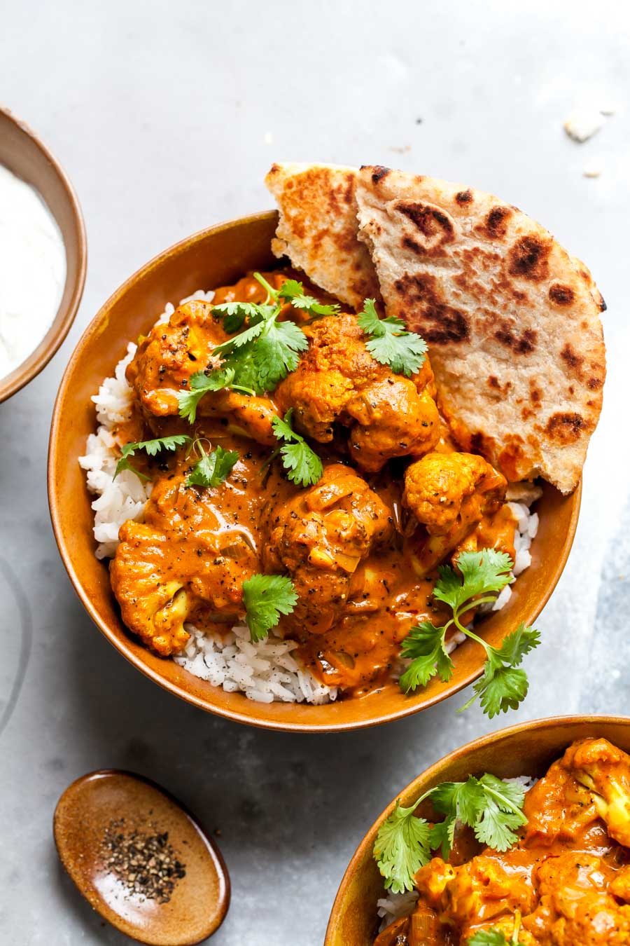 Vegetarian Butter Cauliflower recipe served over basmati rice with yogurt and naan