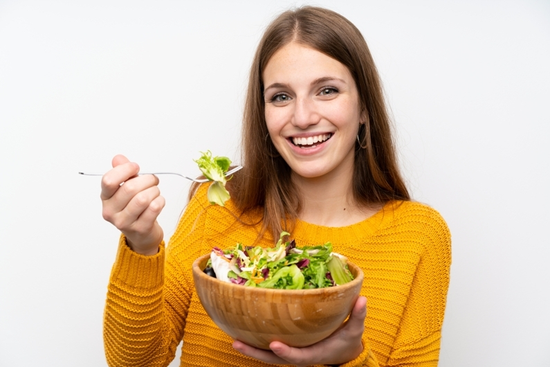 Young woman with long hair holding salad bowl