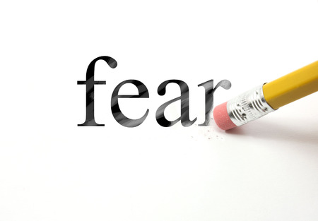 24825176 - the word fear written with a pencil on white paper. an eraser from a pencil is starting to erase the word fear.