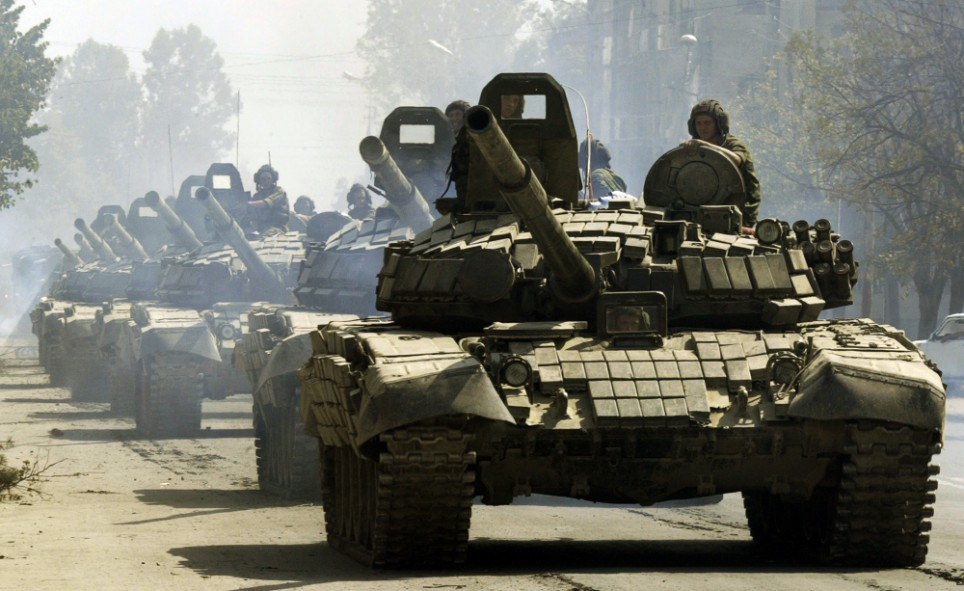 """Russian tanks drive through Tskhinvali, the regional capital of Georgia's breakaway province of South Ossetia, moving to the Russian border, Saturday, Aug. 30, 2008. Georgia has severed diplomatic ties with Moscow to protest the presence of Russian troops on its territory, and its president cast the far-confrontation over his country's fate as """"a fight between the civilized and the uncivilized worlds."""" (AP Photo/Dmitry Lovetsky)"""