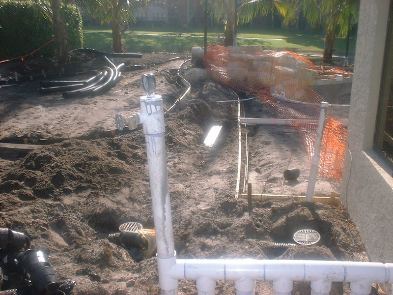 When is a good time to install drainage work if you're building a new pool and it's needed ? This question we get from time to time and this photo shows the stage where it's best to have the drainage installed. It can be done at a later stage, even after completion, but once the pool shell is formed and the plumbing is done, then a rough grade by machine is performed to level off the construction area and remove the soil that is needing to be taken off the property from the pool dig. Before the irrigation, it can be done in unison with the irrigation or at least before the paver decking if water needs to be routed away from gutter downspouts that would pour onto a pool deck if no drainage piping is installed. A note : if your home has gutter downspouts that will empty onto the surface of your new pool or patio decking, it can be handled at this point easily, before the pavers are installed.