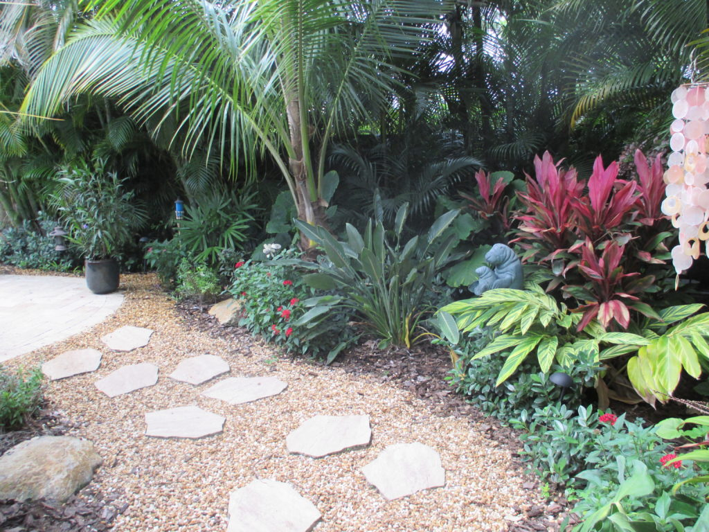 Photo shows a Chattahoochee stone pathway with concrete, natural shaped step stones that were used, leading through a new landscape in this tropical styled backyard.  This corner section of the backyard was a finishing touch to a new pool being constructed, helping to provide a frame to the corner of this relaxed backyard setting.  Hope you like !