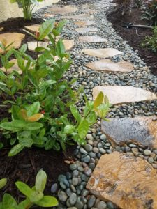 "This pathway was done with the completion of a new swimming pool in the backyard. The smaller stone is a 3/4"" Mixed Mexican Beach pebble which provides a clean accent and contrast with the Crab Orchard stepping stones.  A low maintenance alternative to lead an easy path from the front of the home to the backyard for yourself or guests."