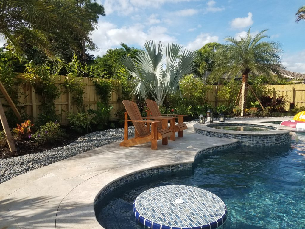 This tropical landscape for this pool included a variety of palm trees as an accent to set a Resort Style tone for this back yard. In view are 2 Sylvester Palms, the Grey/Silver Bismarkia palm between them - and the desired tall evergreen backdrop to grow in is started here with 5' Fishtail palms.  The stone accent helps to keep a cleaner look as well as providing a more spacious feel while tying in with the colors of the deck and pool tile. Hope you like !