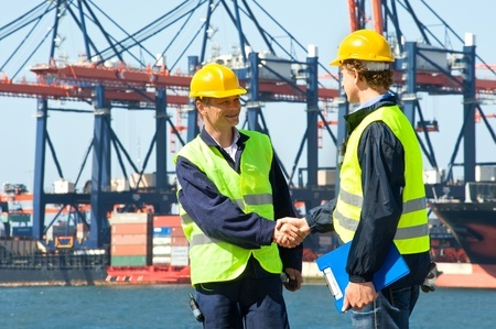 two workers shaking hands at seaport