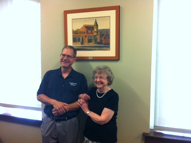 Maplewood librarian Terrence Donnelly and Carlene Masters, who donated the Stan Masters painting to the library.