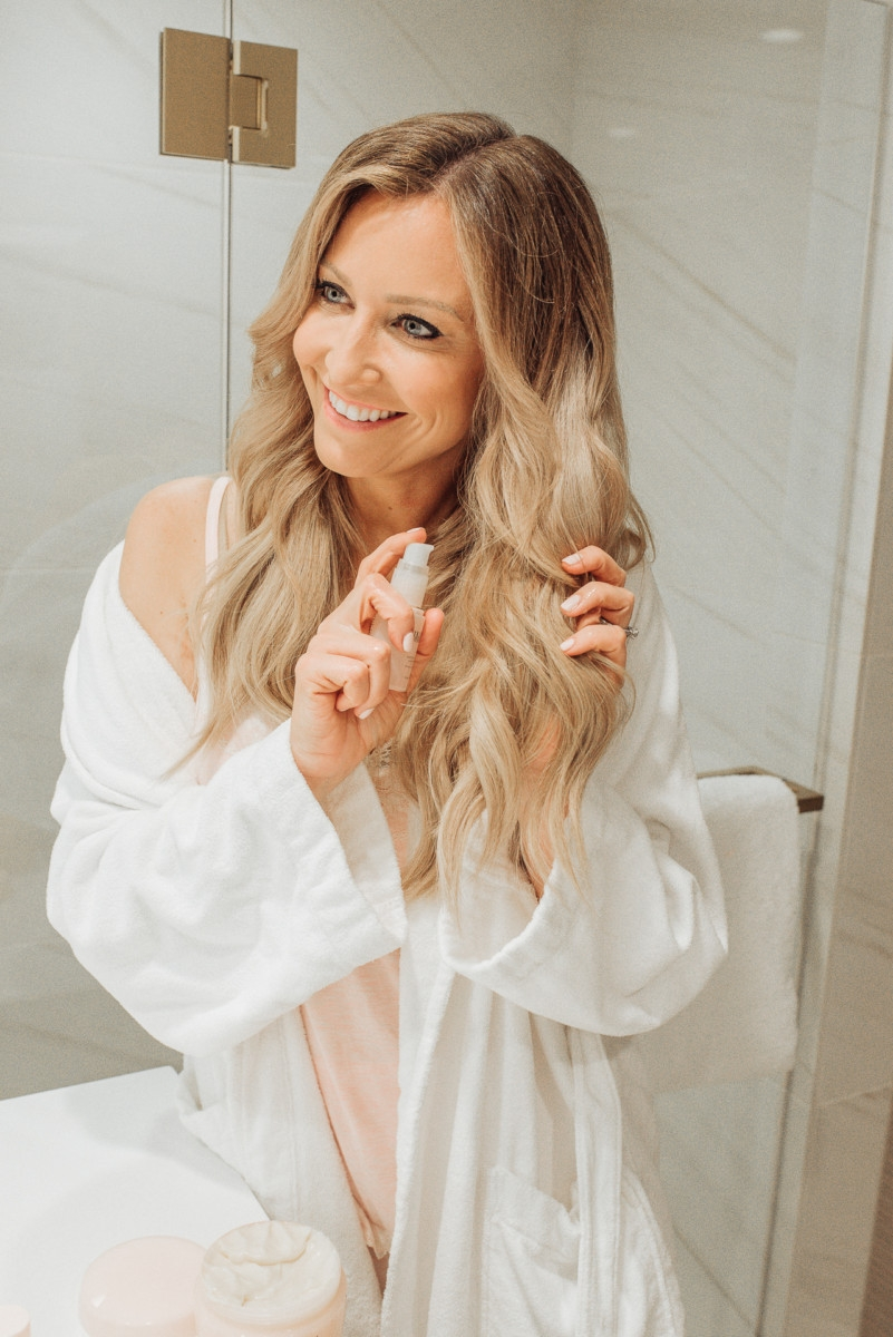 Healthy Shiny Hair featured by top US beauty blog Haute & Humid; Image of a woman in her bathroom.