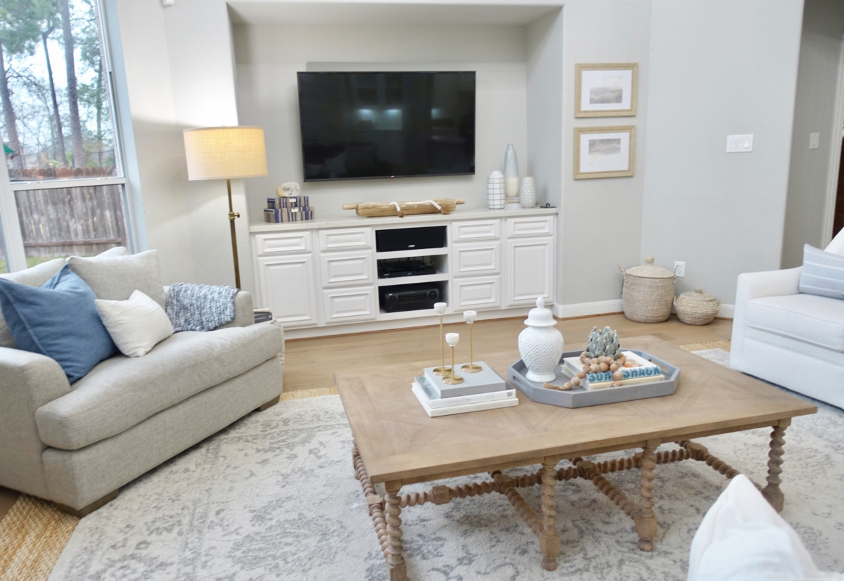 living room remodel | Living Room Makeover by popular Houston lifestyle blog, Haute and Humid: image of a remodeled living room with a Wayfair Shayla 20-Light Candle Style Wagon Wheel Chandelier, Wisteria Barley Twist Coffee Table, and Perigold ARIANA VERNAY RECTANGULAR CONSOLE TABLE.