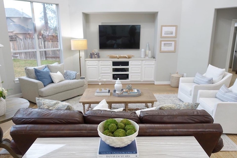 living room decor | Living Room Makeover by popular Houston lifestyle blog, Haute and Humid: image of a remodeled living room with a Wayfair Shayla 20-Light Candle Style Wagon Wheel Chandelier, Wisteria Barley Twist Coffee Table, and Perigold ARIANA VERNAY RECTANGULAR CONSOLE TABLE.
