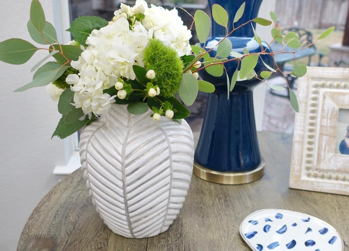 living room decor | Living Room Makeover by popular Houston lifestyle blog, Haute and Humid: image of a remodeled living room with coffee table containing a white flower vase, wood picture frame, and blue lamp.