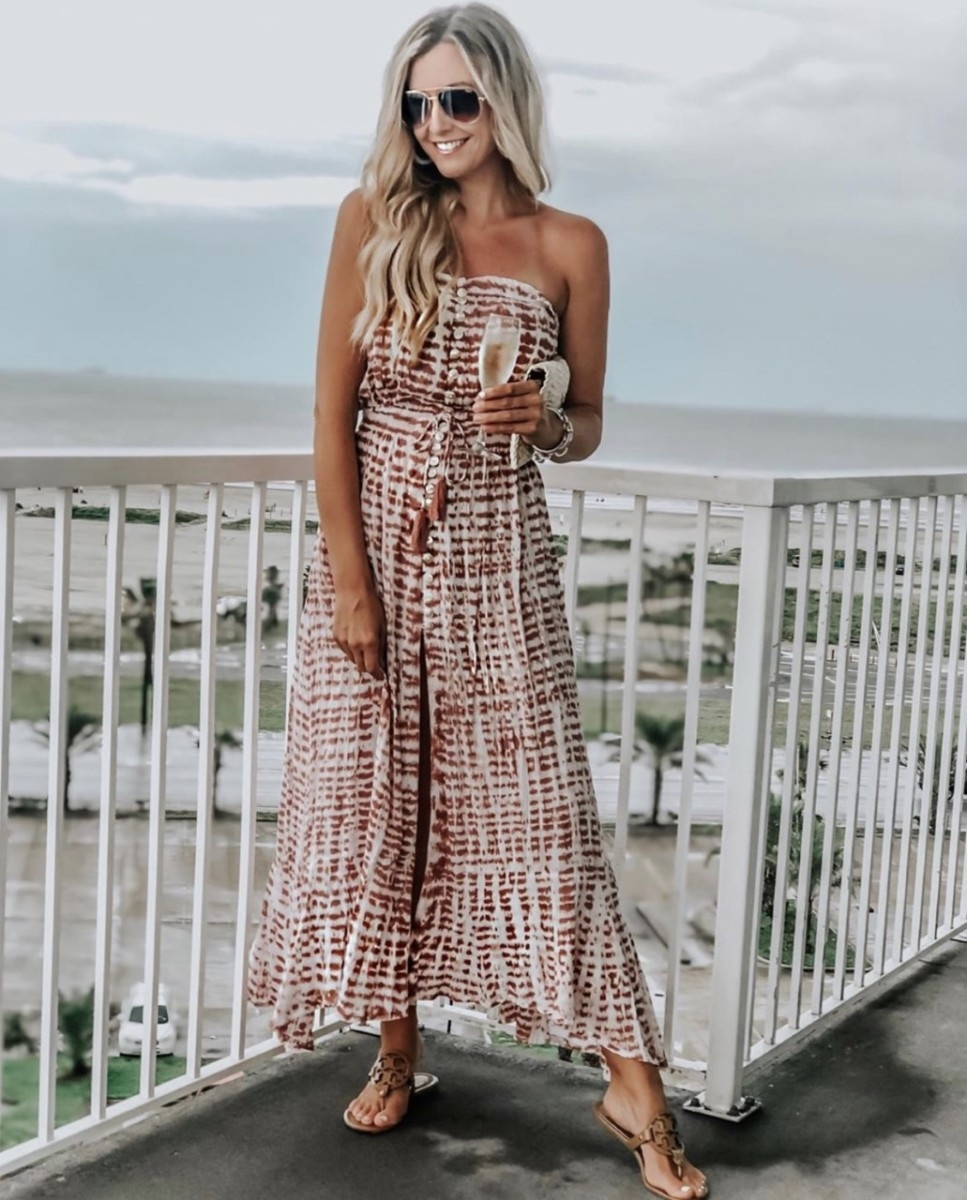 maxi dress | Complete Guide To Affordable Resort Wear by popular Houston fashion blog: image of a woman wearing a Ryden Dress Tiare Hawaii brand: Tiare Hawaii, Nordstrom Quay Australia x JLO All in 56mm Aviator Sunglasses, Amazon Kusmy Straw Clutch Handbag, and Nordstrom Miller Flip Flop TORY BURCH.