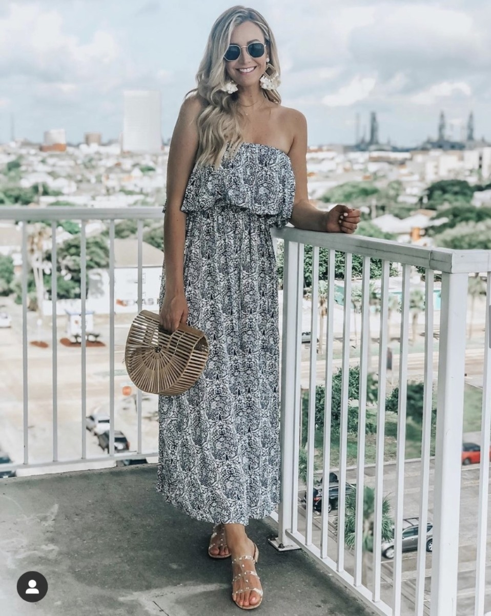 floral maxi dress | Complete Guide To Affordable Resort Wear by popular Houston fashion blog: image of a woman wearing a Amazon Yidarton Women Summer Blue and White Porcelain Strapless Boho Maxi Long Dress, Amazon Miuco Womens Bamboo Handbag Handmade Large Tote Bag, Amazon Jessica Simpson Women's Caira2 Flat Sandal, and Amazon Meangel Rattan Tassel Earrings for Women Bohemian Statement Handmade Woven Drop Dangle Earrings.