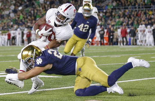 Stanford running back Bryce Love is tackled by Notre Dame defender Drue Tranquill during the first half.