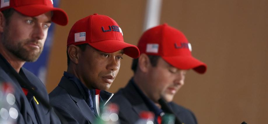 US players Webb Simpson, left, Tiger Woods and Patrick Reed, right, attend the press conference of the losing team after Europe won the 2018 Ryder Cup golf tournament at Le Golf National in Saint Quentin-en-Yvelines, outside Paris, France, Sunday, Sept. 30, 2018. (AP Photo/Alastair Grant)