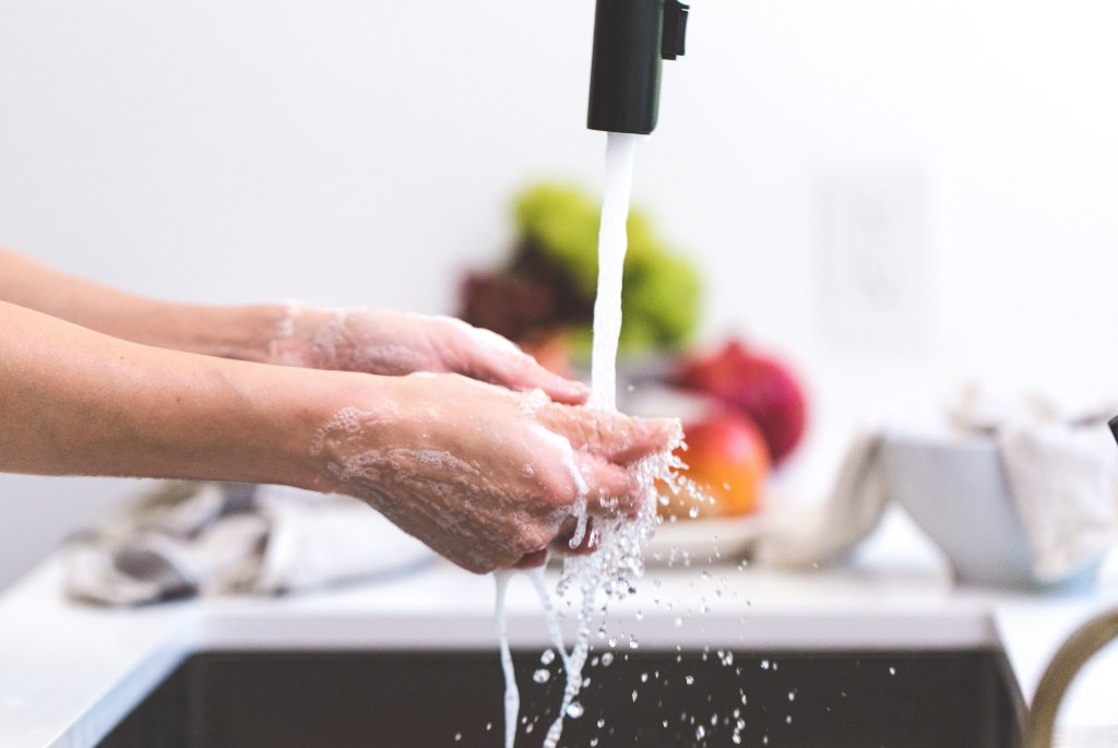 Woman washing hands at faucet