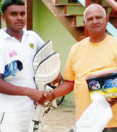 Sam Sooppersaud (right) presents cricket gears to young Alex Algoo during his visit to Guyana in July. Photo courtesy of Kaieteur News.