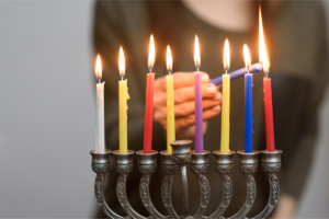Person lighting the last Hanukkah candle on the menorah