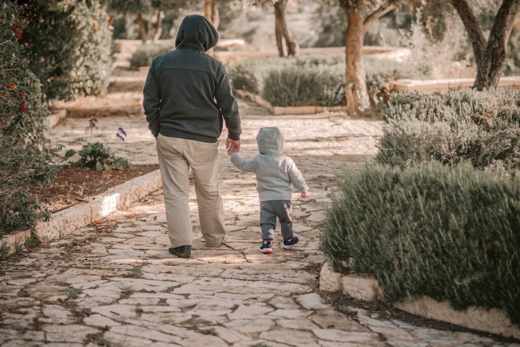 Dad and child walk through garden with hoodies on