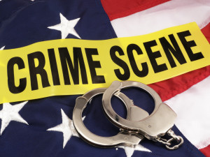 News Concept: Hand Cuffs And Crime Scene Cordon Tape Over American Flag - Suggests Crime In American And Police Response