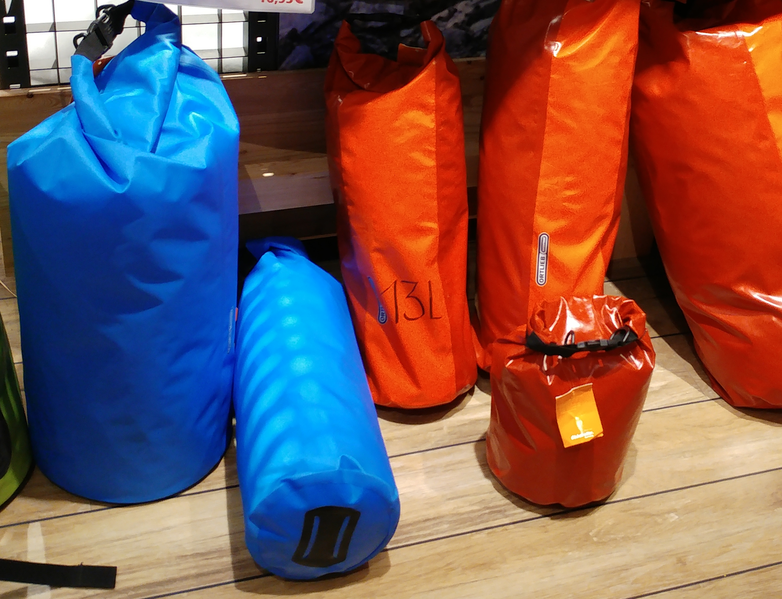Blue and orange dry bags on a wood floor
