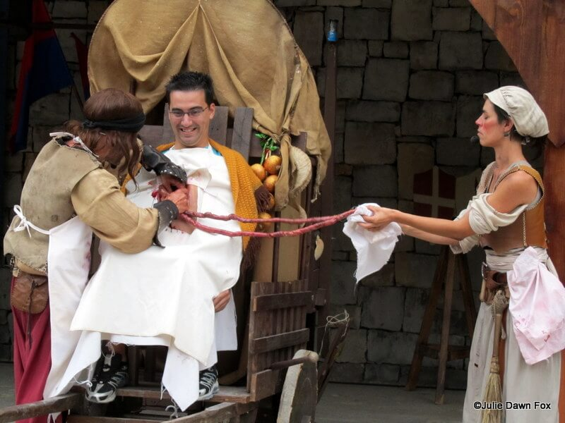 Actors pull fake intestines from a willing suspect. Comedy act, Obidos medieval fair