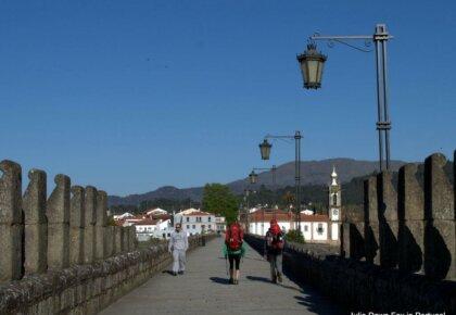 Pilgrims crossing the ancient bridge in Ponte de Lima on the Portuguese Way of St. James