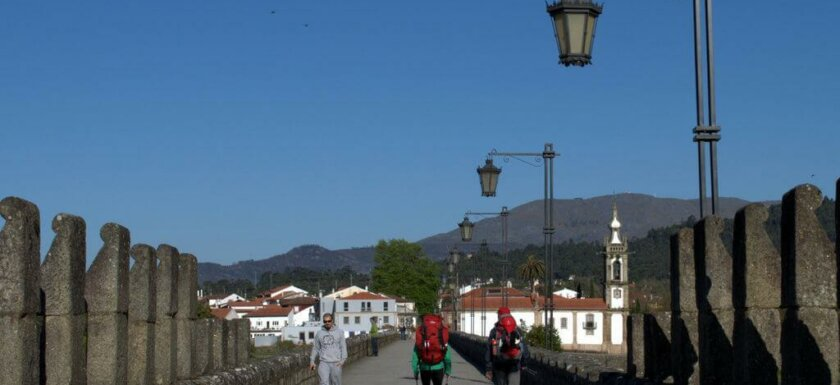 Pilgrims crossing the ancient bridge in Ponte de Lima on the Portuguese Way of St. James