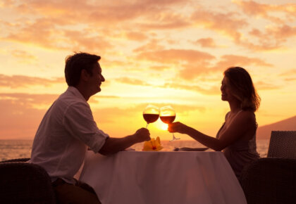 Couple sharing romantic sunset dinner on the beach. Romantic getaways in Portugal