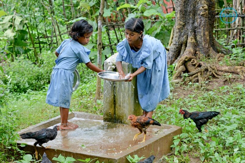 Two girls washing a plate at an outdoor tap.